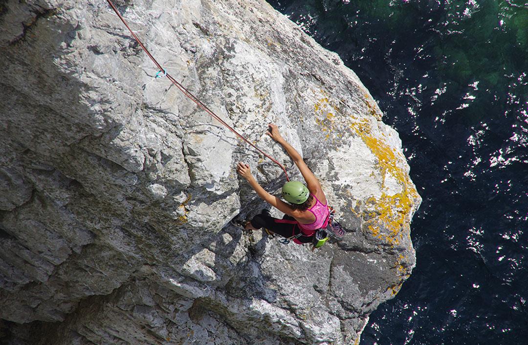 Photo aérienne d'une personne encordée, escaladant un rocher au dessus de l'eau - référence