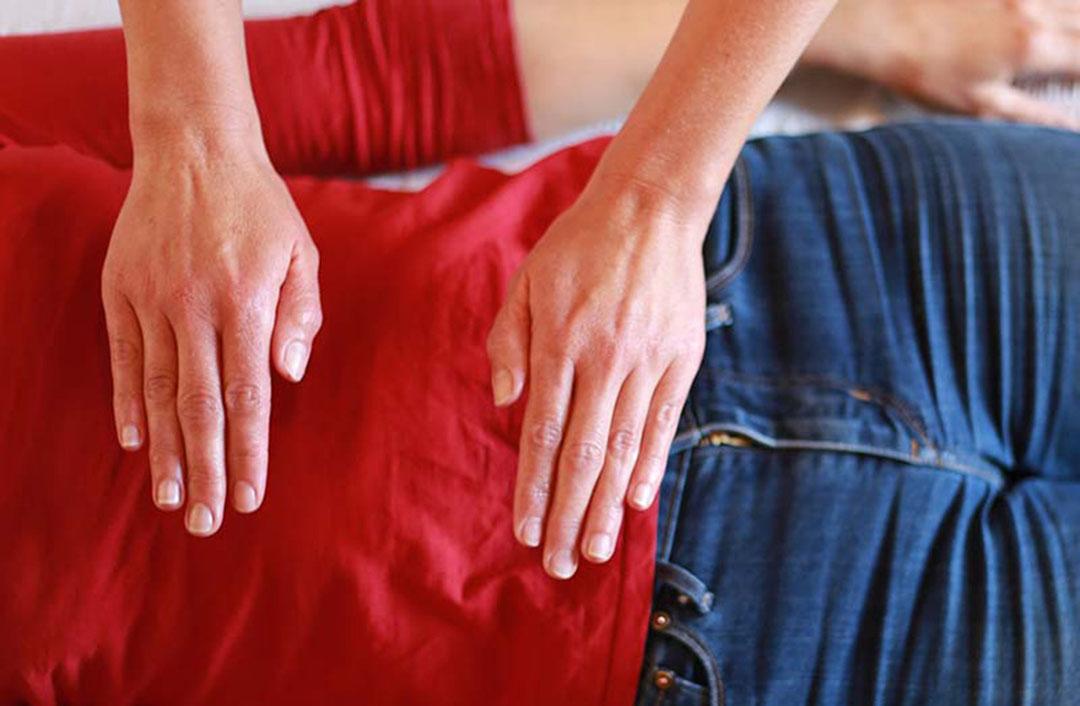 Photo de deux mains en soin d'une personne allongée - référence