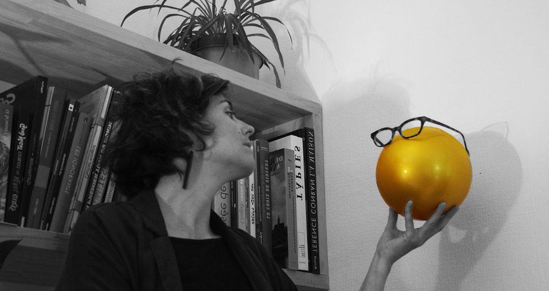 Portrait photo d'Amélie Clergeau en noir et blanc avec balle dorée devant bibliothèque - mot conte double